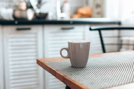 Hot cup of tea or coffee, cocoa on wood table in kitchen background. Good morning wake up concept
