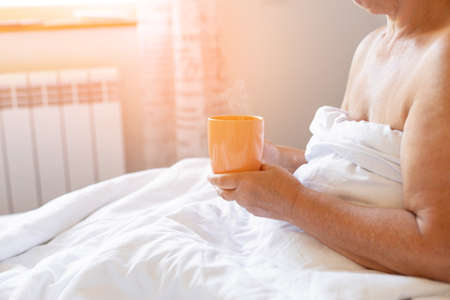 Female hand with cup of hot drink in bed. Good morning wake up concept.