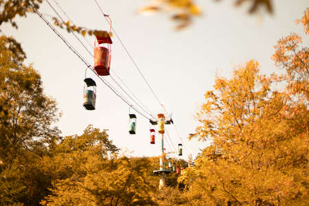 Cable car with colorful cabs over green forests with blue cloudy sky on the background. Autumn time
