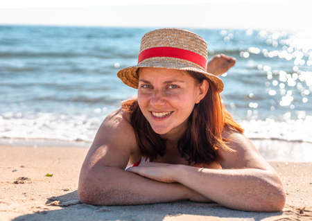 Happy woman in a hat and swimsuit lies, relaxing on the beach, looking at the camera