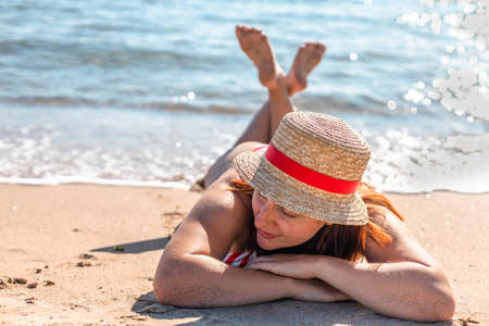 Happy beautiful woman in a hat and swimsuit lies, relaxing on the beach, looking at the camera. Travel vacation lifestyle concept