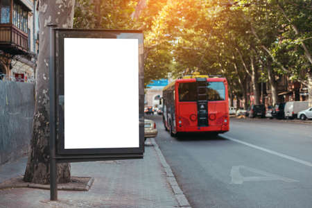 Vertical billboard lightbox mock up for advertisement, banner near street road. Red bus travels on a dedicated line in the city
