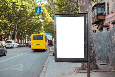 Blank mock up vertical street billboard in busy city street. Yellow bus travels on a dedicated line in the city