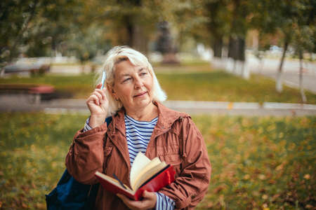 Portrait of thoughtful concentrated busy senior woman having notepad and pen in hands planning, expertising, thinking. Education, studying foreign languages concept, copy space. Stock Photo