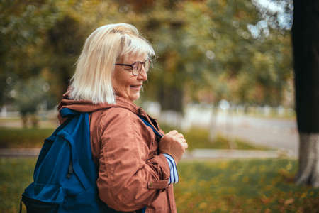Caucasian European blonde smile woman tourist with a backpack travels, enjoying beautiful nature while nordic walking in pine forest.