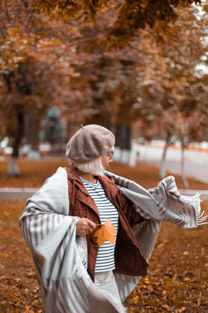 Happy caucasian woman in french warm beret and woolen blanket whirls and enjoys in the park, autumn day Stock Photo