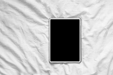 Top view mockup image of blank screen tablet on cozy white bed at home