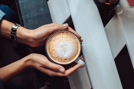 Female hands hold hot mug with cappuccino on glass table in cafe
