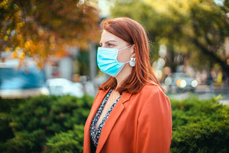 Coronavirus, covid 19 concept. Young girl in a medical mask and suit holds a smartphone in her hands and looks to the side on the street