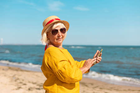 Close up of cheerful young blonde girl in summer hat taking a selfie at the beach. Portrait of a happy young woman smiling at the sea