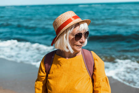 Woman traveler in summer hat and sunglasses stands on the beach and enjoys a beautiful view