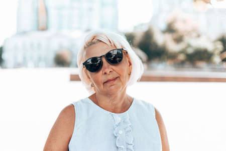 Portrait of blonde positive satisfied mature woman in sunglasses looks at the camera outdoors in park