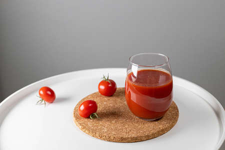 Tomato juice in glass and tomatoes on white coffee table. Minimal creative composition