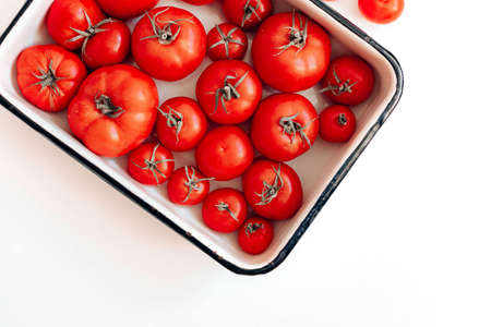 Ripe tomatoes of different sizes in a metal dish on a white plate with a copy space