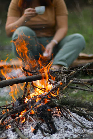 A young girl drinking a hot drink in the background, shallow depth of field. Bonfire in the forest for grill or bbq picnic