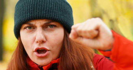 Angry young girl with raised fists. Feminism, power concept. Protest against violence, discrimination. Struggle for rights. International Womens Day.