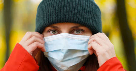 Young woman wearing a warm hat and a protective medical mask to protect against viruses, germs during the coronavirus pandemic in the world Stock Photo
