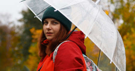 Young girl in warm clothes with a transparent umbrella and a backpack on her back outside in cold weather after rain. Woman looks at the camera.