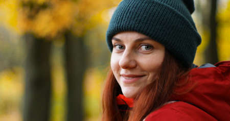 Young girl in warm clothes looks into the camera and smiles outside in cold weather after the rain. Stock Photo