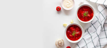 Borscht or traditional Ukrainian soup made of beet, tomatoes, cabbage, carrots and meat in ceramic bowls with copy space on white background