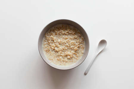 Homemade oatmeal porridge with milk in bowl on a white background. Health nutrition food concept Stok Fotoğraf