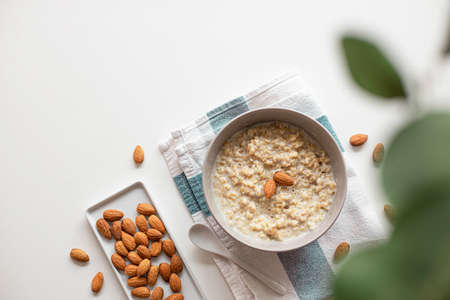 Creative layout made of homemade oatmeal porridge with nut almonds in bowl, ceramic spoon on white background. Healthy eating and lifestyle concept