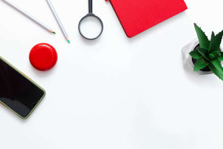 Creative office desk. Red notebook, smartphone, plant, wireless headphones and pencils on white plain minimalistic background with copy space. Freelance work concept Stok Fotoğraf