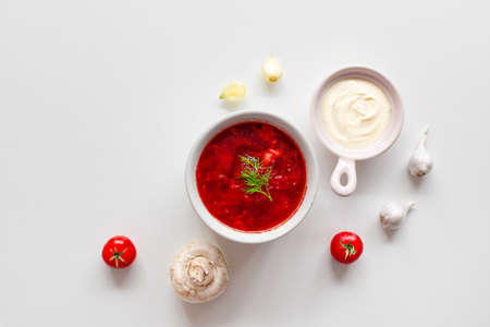 Homemade Traditional Ukrainian beet soup with fresh green dill. Russian borscht in bowl of tomatoes, sour cream, and mushrooms on white background with copy space.