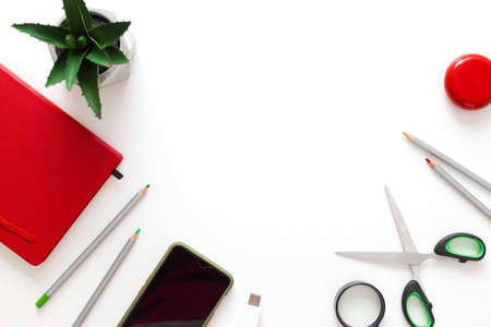 Red notebook, plant, smartphone, wireless headphones and pencils on a white plain minimalistic background with copy space. Freelance office workplace work concept