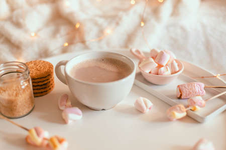 Delicious sweet aromatic cocoa drink or hot chocolate with marshmallow sweets in mug on white table. Warming Christmas winter drink. Decoration garlands of lights