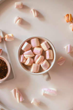 Ceramic cup of hot chocolate or cocoa with marshmallow on a white table. Decoration garlands of lights. Flat lay, top view Stok Fotoğraf