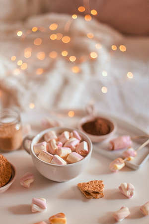 Decoration garlands of lights. Ceramic cup of hot chocolate or cocoa with marshmallow on white table.