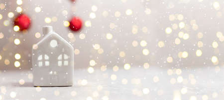 Christmas small toy model house and red balls on white table with light blurred wall background. Holiday template horizontal composition