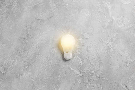 Idea illuminated light bulb on grey background. Creative inspiration, planning ideas concept. Flat lay, top view with copy space 版權商用圖片