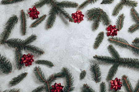 Christmas and New Year holiday background. Creative frame made of Christmas fir branches, red bow on grey background. Flat lay, top view, copy space