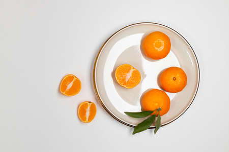 Fresh tangerine or clementin fruits on a beige plate with a gold rim on the table. Colorful fruit background. Flat lay, top view, copy space. Decorative christmas holiday composition