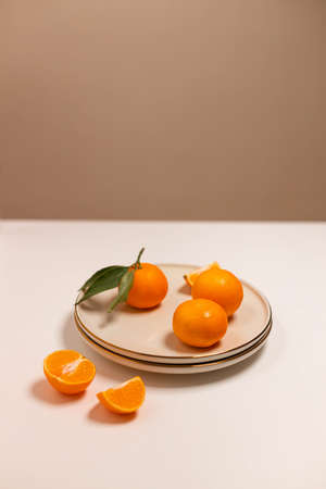 Fresh tangerine or clementin fruits on a beige plate with a gold rim on white background. Colorful fruit background. Decorative christmas holiday composition