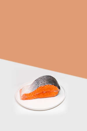 Single fresh raw salmon steak on the edge of white table. Orange shot background. Creative minimalist mockup with copy space
