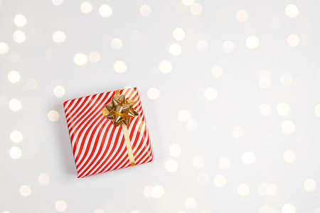 Cozy holiday composition. Gift box wrapped in striped red paper with a gold bow on a white background with copy space. Flat lay, top view. 版權商用圖片