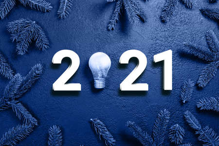 2021 idea minimal concept. Figures with glass glowing light bulb and spruce branches on a dark gradient background. Holiday composition 版權商用圖片 - 161925712