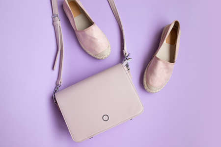 Stylish minimalistic stylish women shoes and premium handbag on purple background, top view, copy space, flat lay. Offers shopping sale concept 版權商用圖片