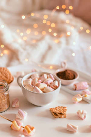 Ceramic cup of hot chocolate or cocoa with marshmallow on white table. Winter dessert beverage. Decoration garlands of lights