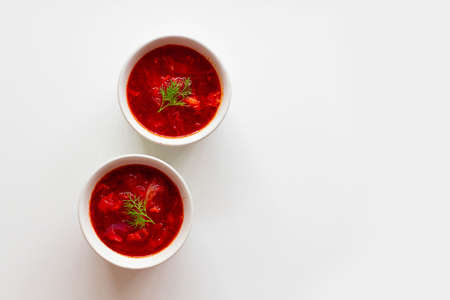 Homemade Traditional Ukrainian beet soup with fresh green dill. Russian borscht in bowl of tomatoes on white background 版權商用圖片