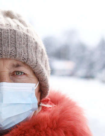 Caucasian woman wearing medical mask looking to the camera at street of city in winter time. Safety in public place during virus outbreak. 版權商用圖片