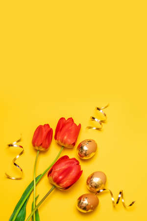 Red tulips bouquet with golden eggs on a yellow background with copy space. View from above. Vertical photo