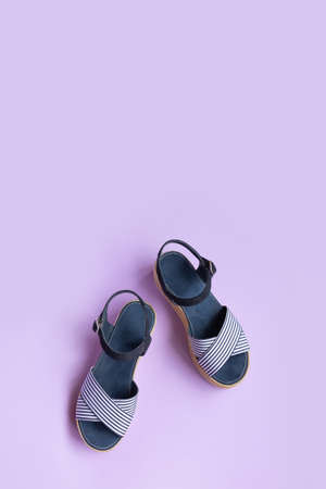 Womens summer striped blue sandals on lilac background with copy space. View from above. Vertical photo