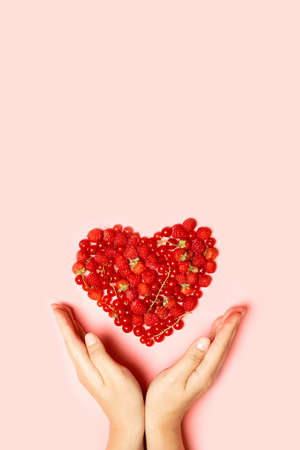 Beautiful fruit heart made of berries with female hands on a pink background with copy space. View from above. Vertical photo 版權商用圖片