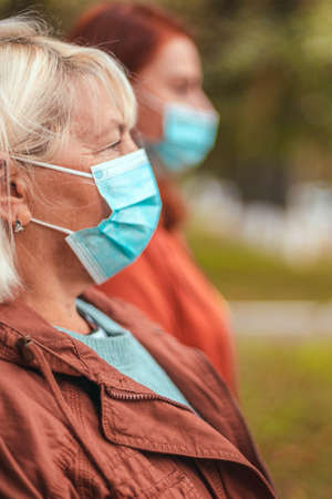People in protective medical masks on the street during the virus, gripe or premonia pandemic. Social distancing. Side view
