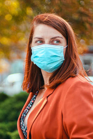 Caucasian woman 20 30 years old in protective medical mask looks away in an autumn park. Safety in public place during virus outbreak.
