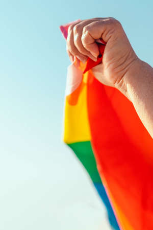 Person hand with rainbow flag flying in bright sun on blue sky background. Vertical photo, close up